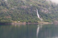 Fjordpier und -wasserfall Stockbild