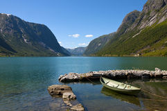 Fjords and boat. A Norwegian landscape, a fjord, a little dock and a boat parked in it. Norway, Sogn & Fjordane county. Fjord landscape Royalty Free Stock Photo