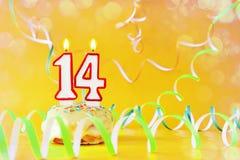 Fjorton år födelsedag Muffin med brinnande stearinljus i form av nummer 14 royaltyfri bild