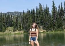 Fjorton åriga Caucasian flicka som lyckligt står i en liten sjö i monteringen Rainier National Park, Washington arkivfoton