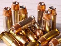Fjorton olika 40 kulor för kaliberfördjupningpunkt tillsammans på en vit träbakgrund arkivbild
