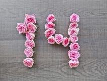 14 fjorton - tappningnummer av rosa rosor på bakgrunden av mörkt trä royaltyfria foton