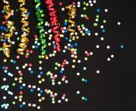 Flámula y confeti coloridos en el papel negro Fotos de archivo libres de regalías