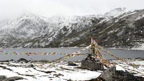 Flâmulas e lago de Sutra abaixo da montanha da neve Imagens de Stock