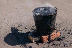 Flüssiger heißer Teer in einem Eimer auf den Ziegelsteinen Dach-Reparatur stockfotografie