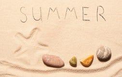 Fläck av sjöstjärnan, havsstenar, sommarbokstäver som dras på sand Arkivbilder