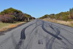 Fläckar för bildäckgummihjulsladdning på den stads- asfaltvägen Arkivbilder