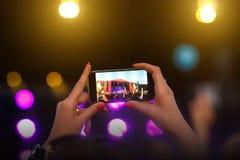 Fläkta att ta fotoet med mobiltelefonen på en konsert royaltyfri foto
