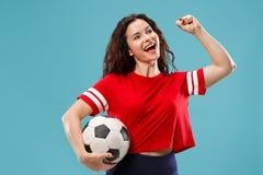Fläkta bollen för fotboll för sportkvinnaspelaren som den hållande isoleras på blå bakgrund arkivbilder