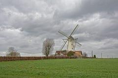 Flämische Ackerlandlandschaft mit traditioneller Windmühle auf einem bewölkten Dy Stockfotos