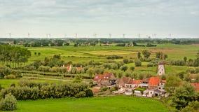 Flämische Landschaft mit Feldern mit Bäumen, alten Häusern und einer Windmühle Stockbilder