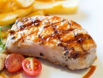 Fläskkotlett Grillad grisköttbiff i den vita maträttserven med den fransmansmåfiskar och tomaten Fotografering för Bildbyråer