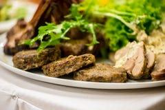 Fläskkotletter, köttsmå pastejer och kallskuret Arkivfoto