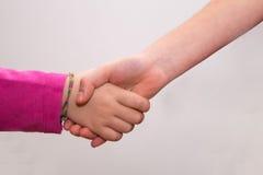 Flätade samman händer av flickor, trycka på för händer Royaltyfri Foto