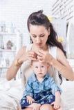 Flätade trådar för modersvans av hår på dotterns huvud Royaltyfria Bilder
