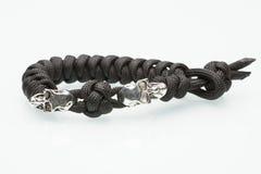 Flätat armband för svart med skallar på vit Arkivbild