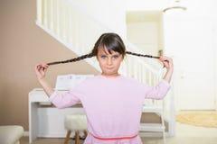 Flätat hår för flickainnehav royaltyfria bilder