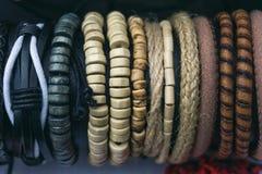 Flätat handgjort läder och träarmbandbakgrund arkivbilder