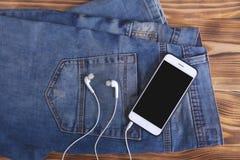 Flåsanden smartphone och hörlurar arkivbild