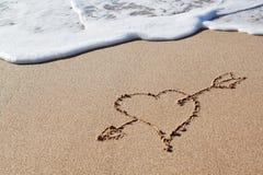 Flèche au coeur dans le sable. Photographie stock