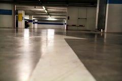 Flèche blanche dessinée au sol dans un stationnement/vieille plaque de rue de flèche sur l'inscription de route/circulation routi Photographie stock libre de droits
