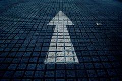 Flèche blanche en avant sur la rue bleue de bloc, ton de bleu de vintage photo libre de droits