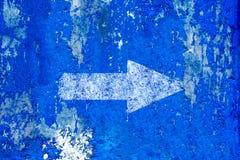 Flèche blanche peinte sur le vieux grunge et le fond bleu superficiel par les agents de texture de mur Photo stock