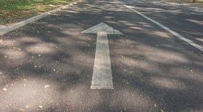 Flèche blanche sur la route Photo libre de droits