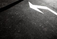 Flèche blanche sur la route de goudron Photographie stock
