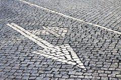 Flèche blanche sur la route en pierre - image de concept Photo libre de droits