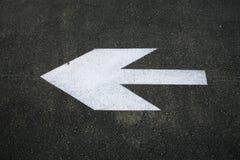 Flèche blanche sur un asphalte noir Image libre de droits