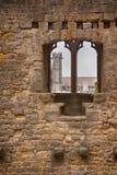 Flèche d'église par un mur médiéval photos stock