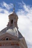 Flèche d'église réglée contre le ciel bleu nuageux Photographie stock libre de droits