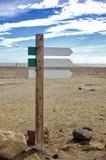 Flèche en bois vide d'enseigne sur le fond brouillé de plage d'océan Calibre de panneau routier Images stock