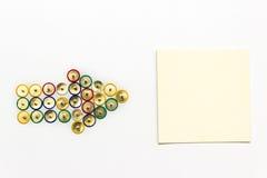 Flèche faite à partir des punaises colorées visant le papier de note Photo stock