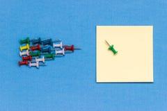 Flèche faite à partir des punaises colorées visant le papier de note Photographie stock libre de droits