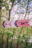 Flèche-indicateur décoratif en gros plan avec l'inscription «love» accrochant sur l'arbre de branche sur la nature images libres de droits