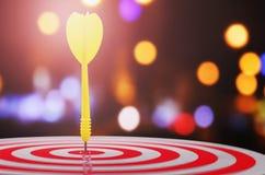 flèche jaune avec le fond et la cible brouillés finis de dartboar Image libre de droits