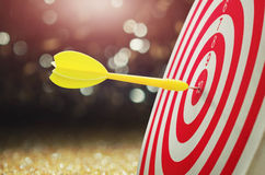 flèche jaune avec le fond et la cible brouillés finis de dartboar Photos stock