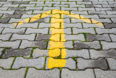 Flèche jaune peinte sur le trottoir gris, signal de direction de route Photos stock