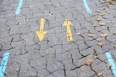 Flèche jaune sur l'allée piétonnière Photographie stock libre de droits
