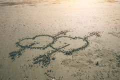 Flèche jumelle de coeur d'amour d'aspiration de symbole de cupidon sur la plage de mer Image libre de droits