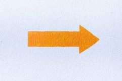 Flèche orange sur le mur en béton rugueux blanc Images stock