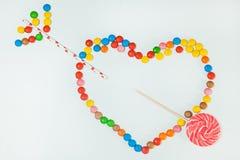 Flèche plate de coeur étendue par fond blanc de lucette de bonbons au chocolat Photo stock