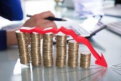 Flèche rouge au-dessus de diminuer les pièces de monnaie empilées photographie stock libre de droits