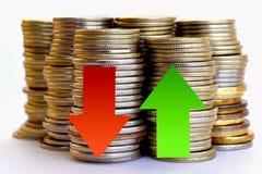 Flèche rouge et verte sur le fond des pièces de monnaie Photographie stock libre de droits