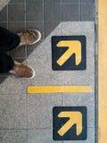 Flèche sur le plancher avec le pied Images stock