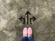 Flèche trois et chaussure rose de pantoufle sur le fond concret images libres de droits