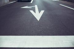 Flèches blanches sur le fond d'asphalte Photos libres de droits