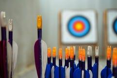Flèches de tir à l'arc avec des cibles dedans hors du fond de foyer Photo stock